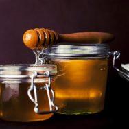 A honey dipper dripping into a pot of honey.